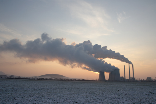 Photo of a power plant with steam/smoke coming out of its towers.